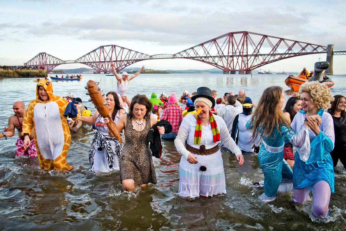 Loony Dook taking place at Queensferry, Edinburgh. Locals run into the sea on the first day of the year, some in fancy dress, with the Forth Rail Bridge behind.